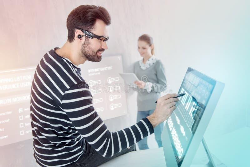 Ruhiger Programmierer, der auf dem Tisch sitzt und in seinem Computer arbeitet stockbilder