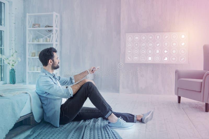 Ruhiger Programmierer, der Fernbedienung beim zu Hause sitzen verwendet lizenzfreies stockbild