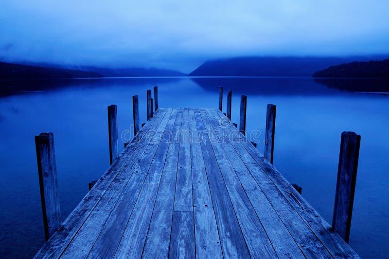 Ruhiger ruhiger See mit blauer Anlegestelle stockfotos
