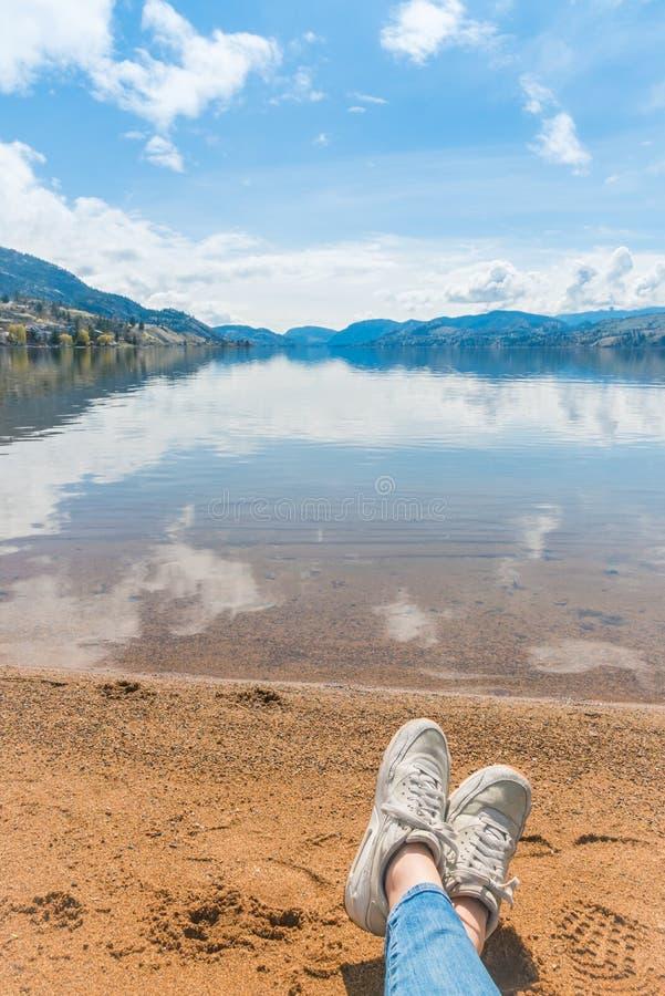 Ruhiger See, der blauen Himmel und Berge mit Strand und Frau ` s Füßen sich entspannen auf Strand auf Vordergrund reflektiert stockfotos