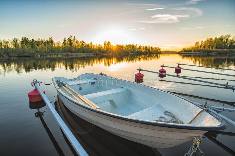 Ruhiger See mit Schilfen bei Sonnenaufgang, Fischerboot gebunden am hölzernen Pier stockbild