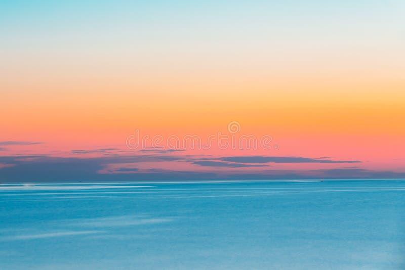 Ruhiger See oder Ozean und bunter Sonnenuntergang-oder Sonnenaufgang-Himmel-Hintergrund stockbild