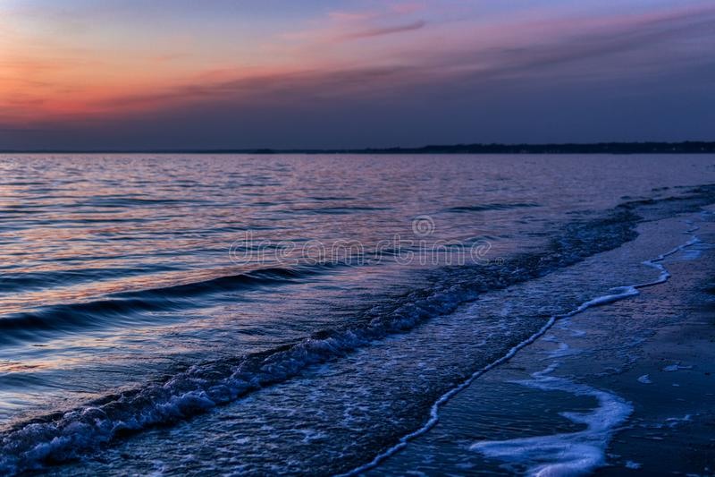Ruhiger Strandsonnenunterganghorizont mit Wellen lizenzfreie stockfotografie
