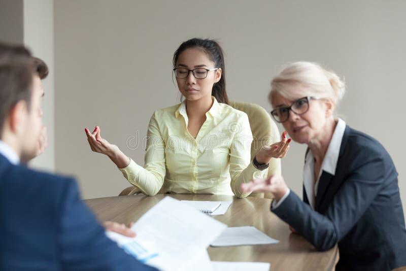Ruhiger weiblicher Angestellter meditieren bei der Sitzung, die Konflikte vermeidet stockfoto