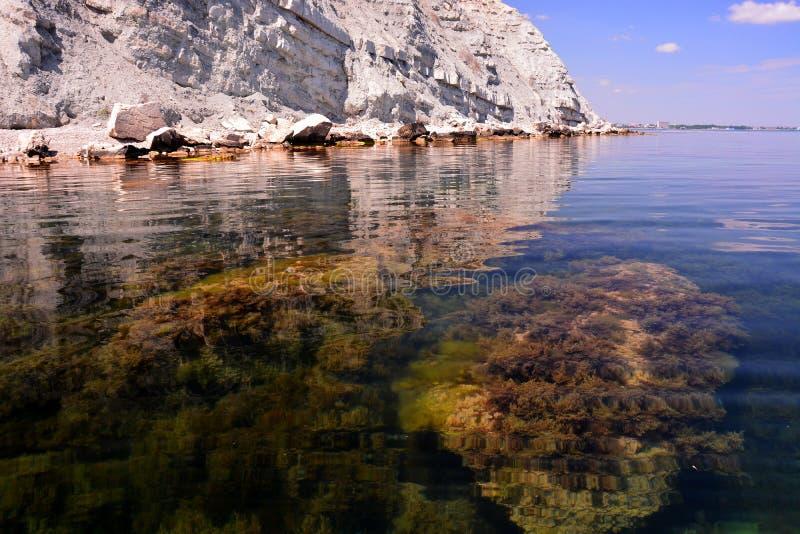 Ruhiges, felsiges Ufer, Unterseite des Meeres und blauer Himmel stockfoto