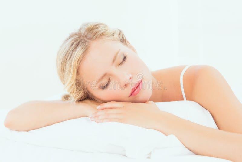 Ruhiges junges blondes Schlafen auf ihrem Bett lizenzfreie stockfotos