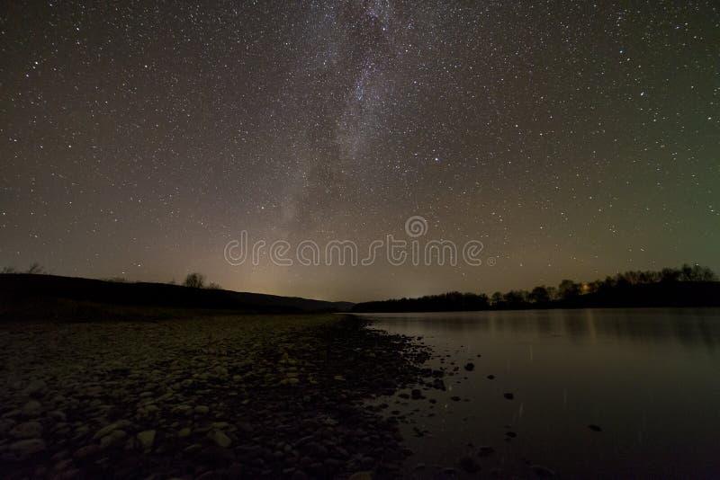 Ruhiges Landschaftspanorama nachts Langer Belichtungsschuß von Kieselflussbank, Bäume auf Horizont, helle Sterne und Milchstraße stockbilder