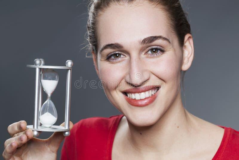 Ruhiges Mädchen 20s mit Symbol des TIMINGs in den Händen lizenzfreie stockfotografie