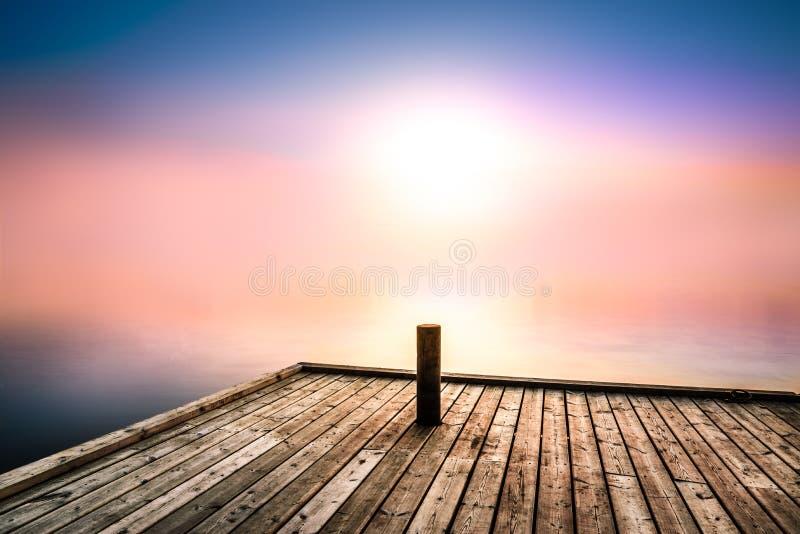 Ruhiges und mysteriöses Bild mit Morgenlicht über einem See stockfotografie
