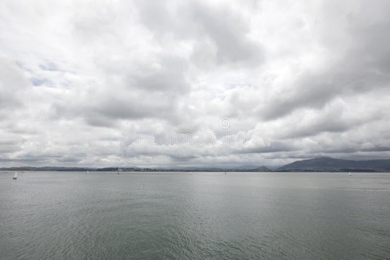 Ruhiges Wasser an einem bewölkten Tag Santander, Kantabrien, Spanien lizenzfreies stockfoto