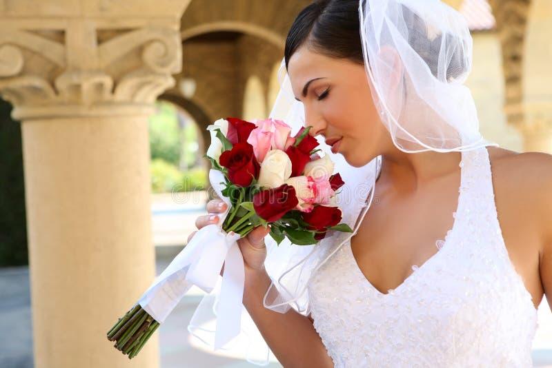 Ruikend het huwelijksboeket van de bruid stock fotografie