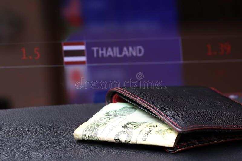 Ruilen THB van het twintig Baht Thaise bankbiljet in zwarte portefeuille op zwarte vloer en digitale raad van munt geldachtergron royalty-vrije stock afbeelding