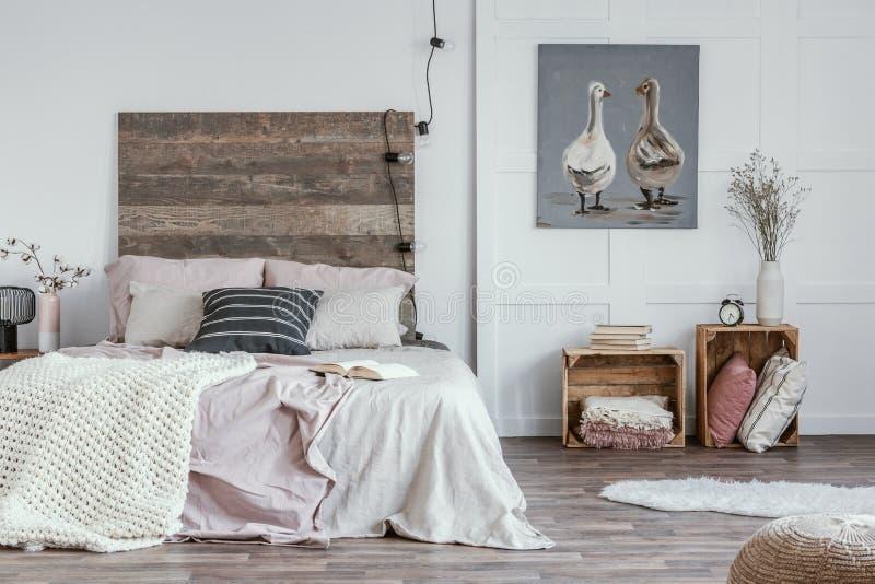 Ruim, vrouwelijk slaapkamerbinnenland met rustiek meubilair, witte muren, houten kratten en olieverfschilderij van dieren Echte f stock foto