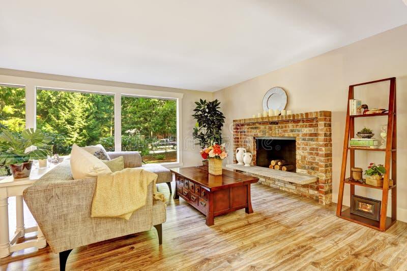 Ruime heldere woonkamer met glasmuur en baksteenopen haard stock afbeelding