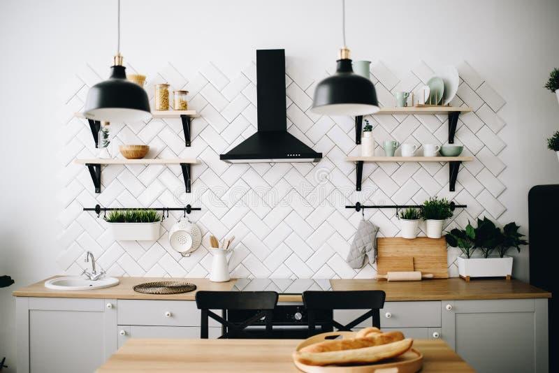 Ruime moderne Skandinavische zolderkeuken met witte tegels en zwarte toestellen Heldere ruimte Modern binnenland royalty-vrije stock foto