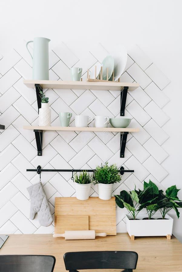 Ruime moderne Skandinavische zolderkeuken met witte tegels en zwarte toestellen Modern binnenland Planken met koppen en platen stock foto's