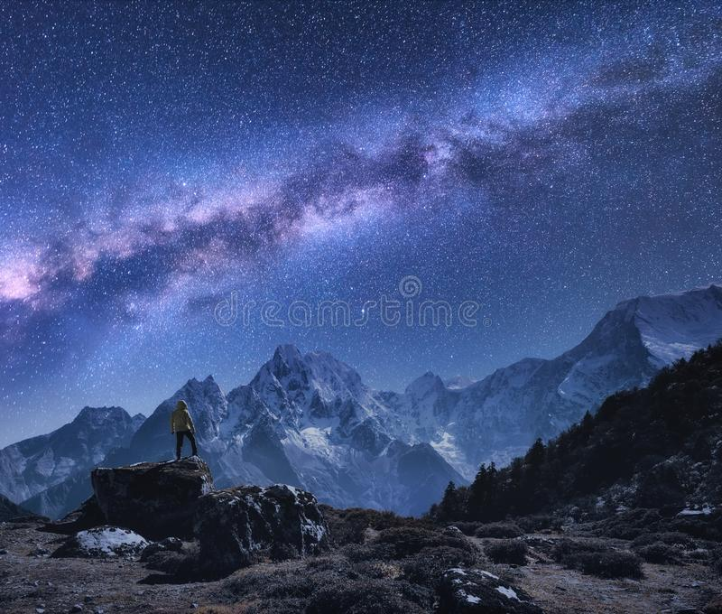 Ruimte met Melkweg, de mens op de steen en bergen stock afbeelding