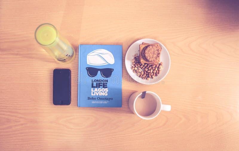 Ruimtegray iphone beside blue labeled-Boek dichtbij Witte Ceramische Kop met Vloeibare Inhoud royalty-vrije stock foto's