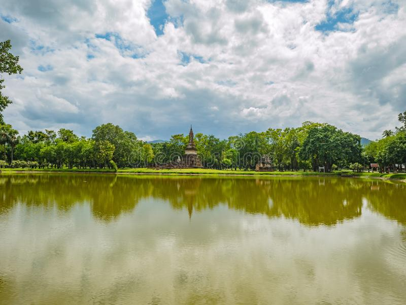 Ruin of Pagoda and statue reflection in the water and nature At sukhothai historical park. Ruin of Pagoda and statue reflection in the water At sukhothai royalty free stock photos