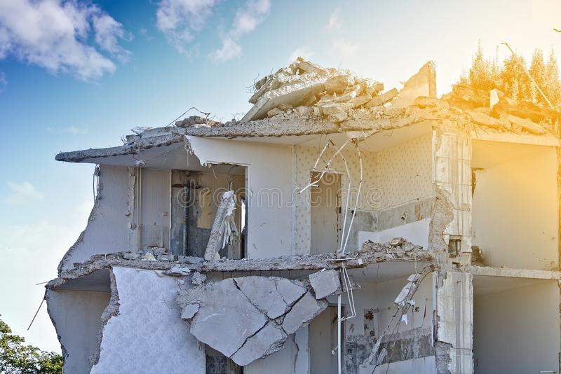 Ruin of a partly demolished residential building upper floor. In front of a blue sky with white clouds stock photography