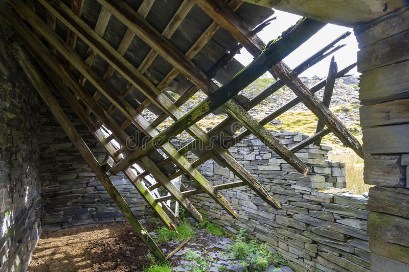 Ruin of stone cottage from within, United Kingdom. Derelict stone building, collapsing roof, Snowdonia, Wales, United Kingdom royalty free stock images