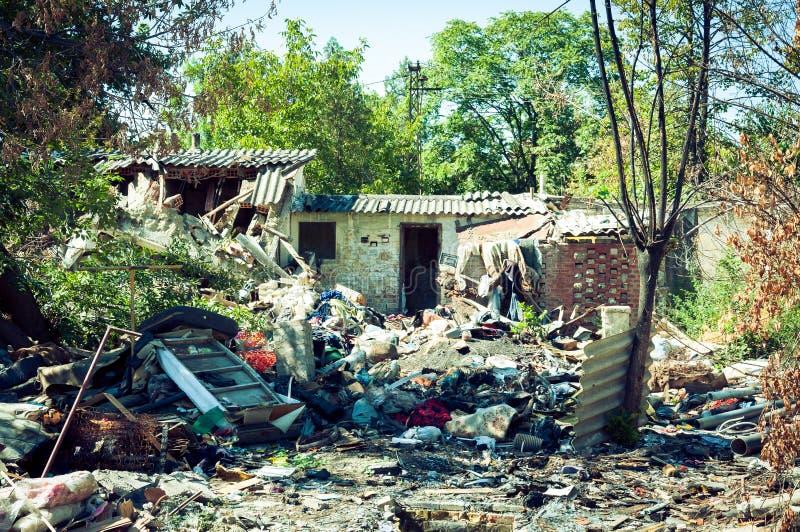 Ruina abandonada de la casa después de la explosión de la granada en el bombardeo con los restos por todo la yarda imagen de archivo