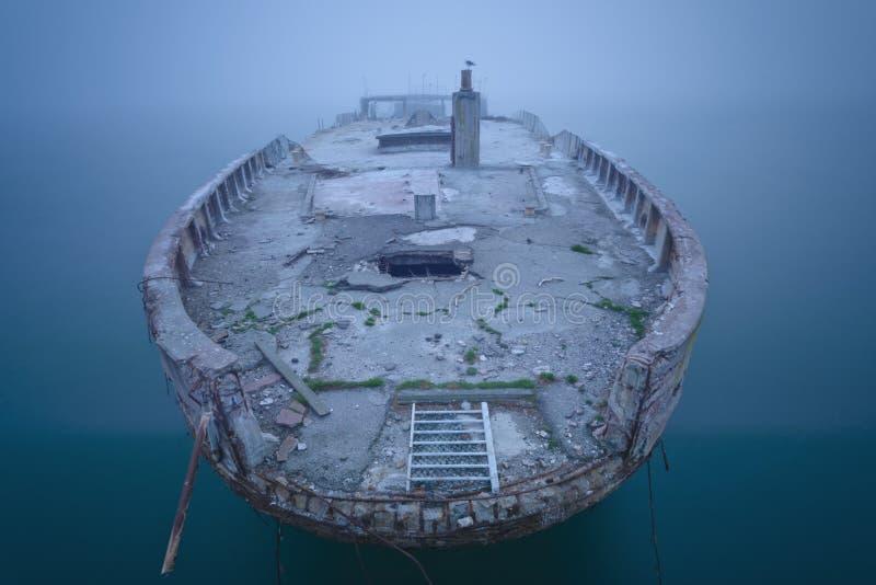 Ruina de la nave en niebla y agua tranquila fotografía de archivo libre de regalías