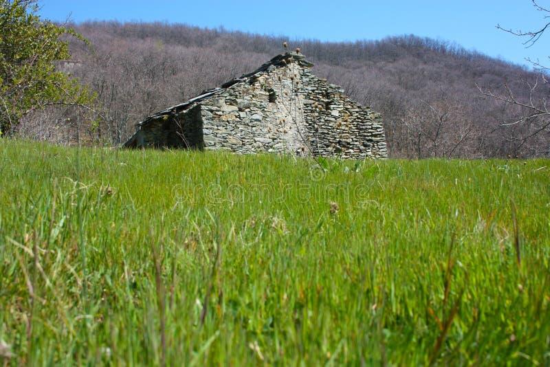 Ruina destruida una casa vieja construida de las piedras abandonadas en un claro verde, en el medio de la naturaleza del parque d imagenes de archivo