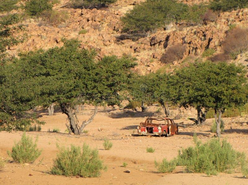 Ruina roja del coche en el desierto imagenes de archivo
