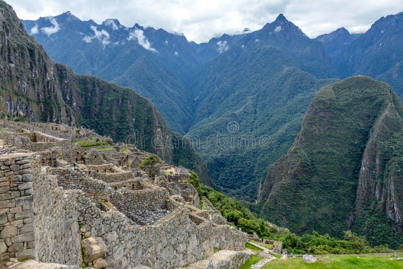 Ruinas abandonadas de la ciudadela Incan de Machu Picchu, del laberinto de terrazas y de las paredes que suben de la maleza grues foto de archivo libre de regalías