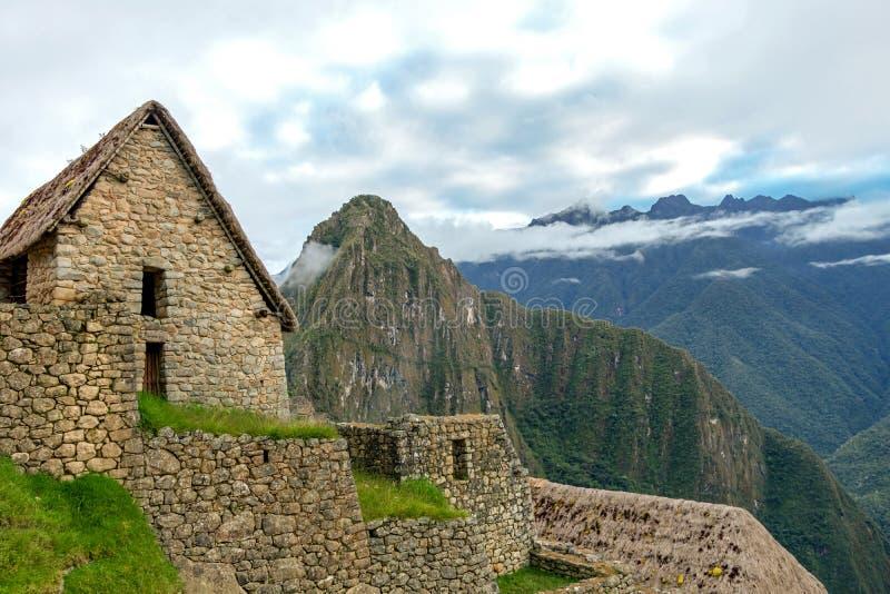 Ruinas abandonadas de la ciudadela Incan de Machu Picchu, del laberinto de terrazas y de las paredes que suben de la maleza grues foto de archivo