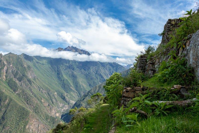 Ruinas antiguas del inca de Pinchinuyok rodeadas por los picos y las nubes de montaña sobre el barranco verde en Perú imagen de archivo libre de regalías