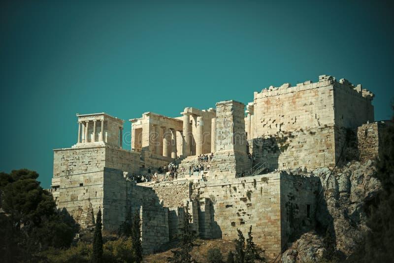 Ruinas de la acrópolis antigua Atenas rodeada por el edificio viejo del parque o del bosque con las columnas en la alta plataform foto de archivo
