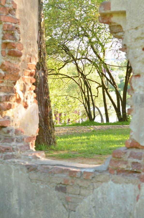 Ruinas de la pared vieja de la piedra del ladrillo con la ventana Pared en el parque con el paso y árboles verdes en el fondo imagenes de archivo