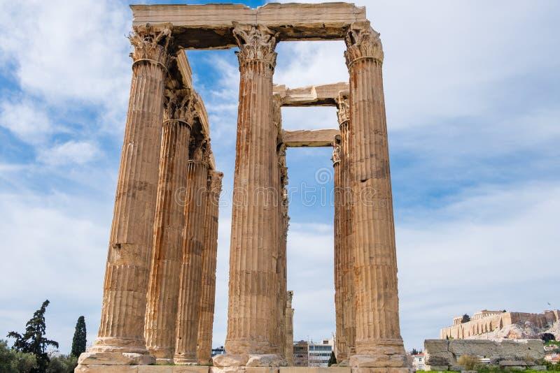 Ruinas del templo antiguo de Zeus olímpico en Atenas con la colina de la acrópolis en el fondo imágenes de archivo libres de regalías