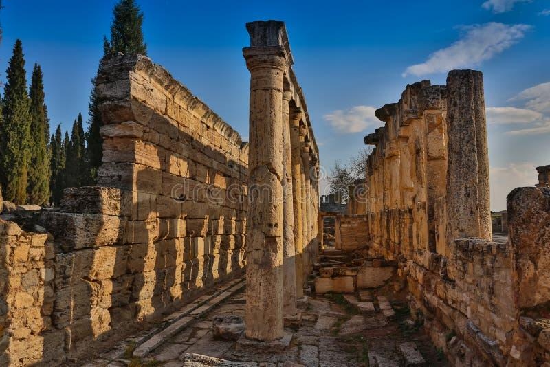 Ruinas del templo de Appollo con la fortaleza en la parte posterior en Corinto antiguo, Peloponeso, Grecia imagen de archivo