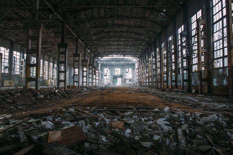 Ruinas espeluznantes oscuras del almacén o del hangar industrial grande abandonado demolido de la fábrica soviética imagenes de archivo