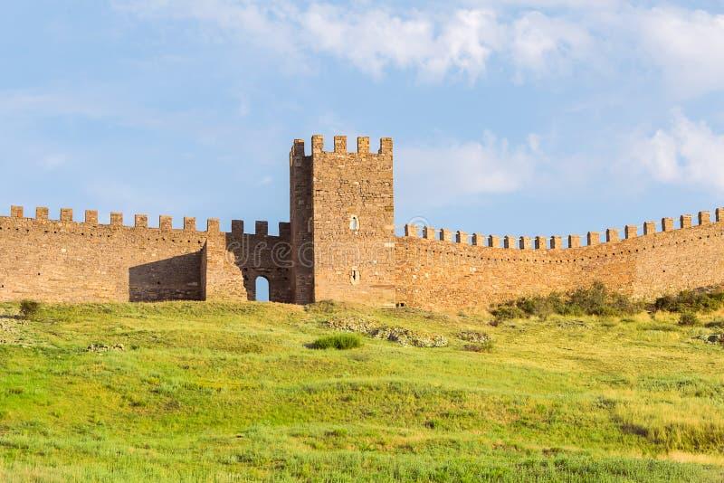 Ruinas Genoese de la fortaleza de Sudak de la viejas torre y parte de piedra de los almenajes en una colina verde fotografía de archivo libre de regalías
