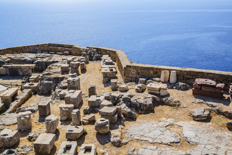 Ruinas y bloques de la piedra de la acrópolis antigua de la ciudad de Lindos contra la perspectiva del mar Mediterráneo Grecia imagen de archivo libre de regalías