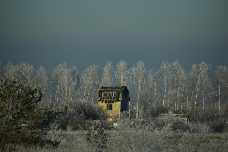 Ruined abandoned house in frozen field royalty free stock images