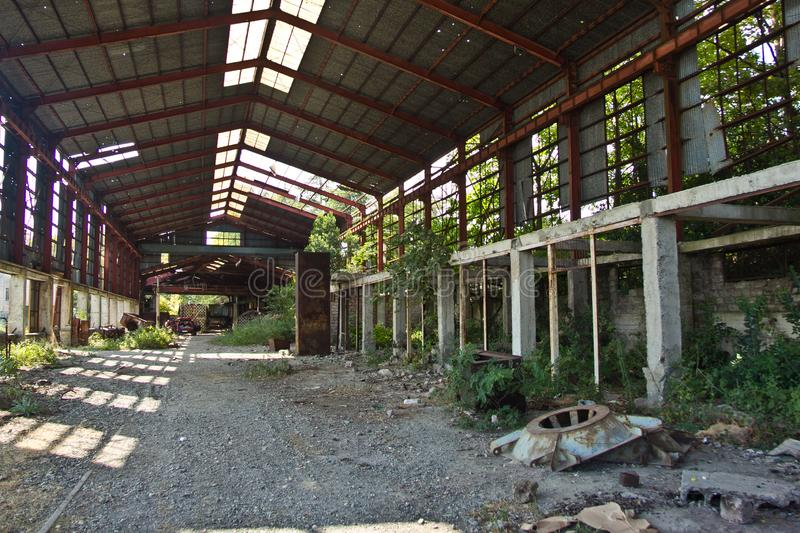 Ruined abandoned industrial building. Overgrown remains of rusty frame stock photos