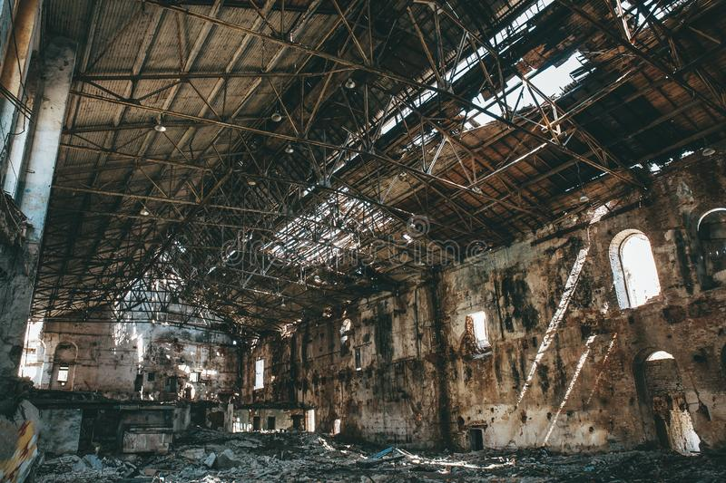 Ruined abandoned industrial factory hall of warehouse or hangar in process of reconstruction. Toned royalty free stock photography