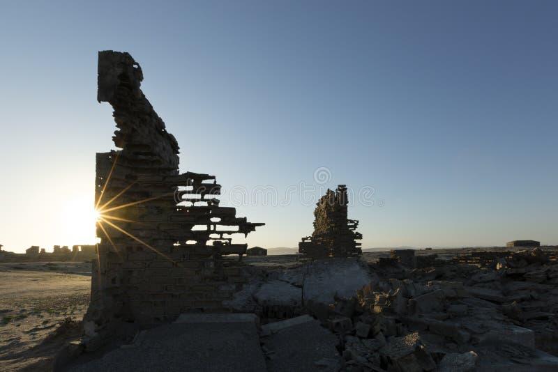 Ruined buildings walls at sunrise. Star burst seen stock photo