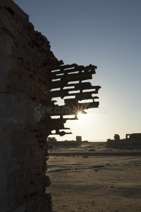 Ruined buildings walls at sunrise. Starburst from sun seen. Bricks missing royalty free stock images
