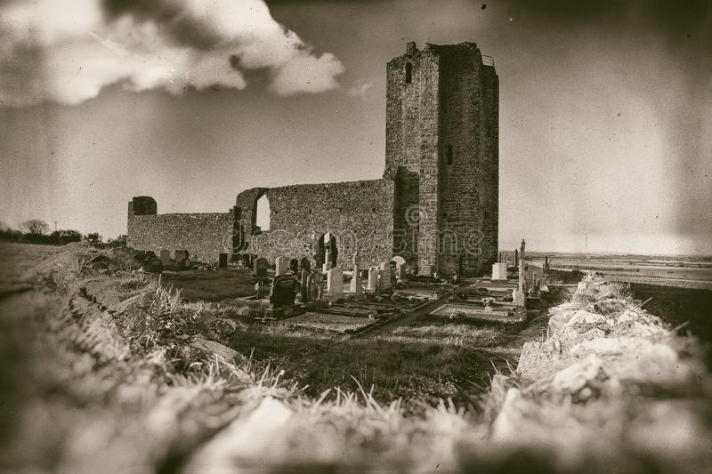 Ancient church ruins with small graveyard surrounded with stone wall in sepia. Ruined and collapsed church with graveyard and churchyard, shot taken from royalty free stock image
