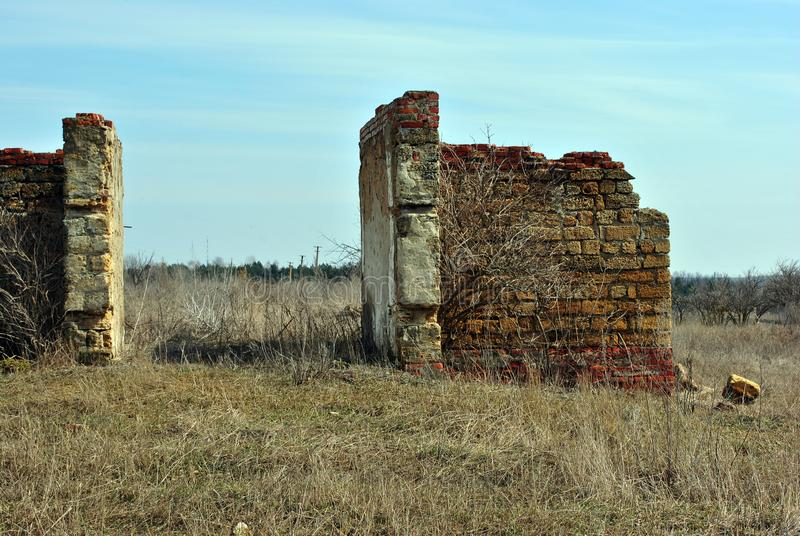 Ruined entrance in farm walls of Crimean coquina rock blocks, dry weathered grass field, blue spring sky royalty free stock photo