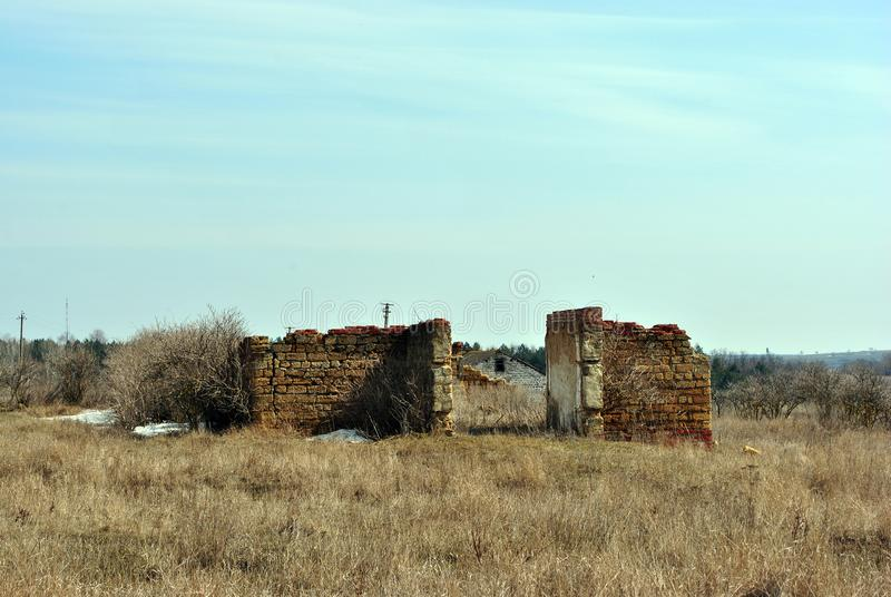 Ruined farm walls of Crimean coquina rock blocks, dry weathered grass field with elderberry bushes without leaves stock images