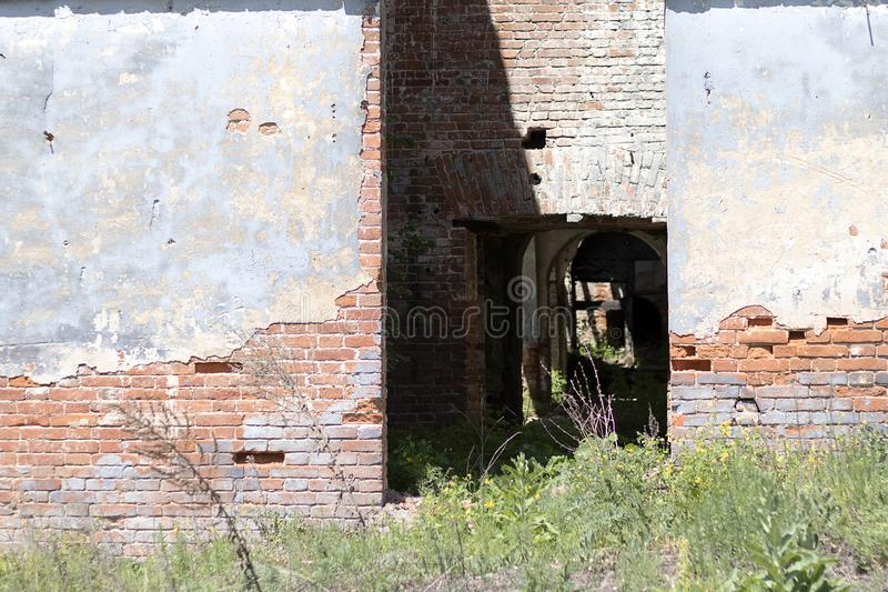 Ruined old red brick building, door to the building. Red brick wall with cement. Green grass in front royalty free stock photo