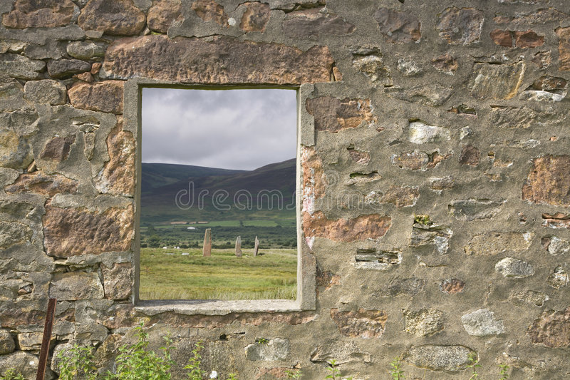 Ruined window. Window frame looking towards neolithic standing stones royalty free stock photography