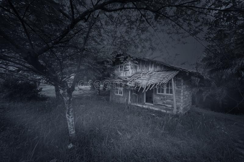 Ruined wood house looks spooky at night. Picture of ruined wood house looks spooky among trees at night time royalty free stock images